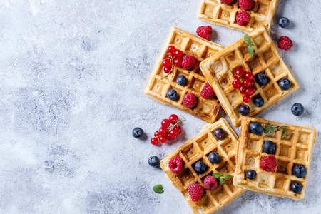 Homemade square belgian waffles with fresh ripe berries blueberry, raspberry, red currant over gray texture background. Top view with space Foto de archivo