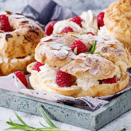 Homemade choux pastry cake Paris Brest with raspberries, almond, sugar powder and rosemary, served on wooden serving tray over gray blue texture background. Close up. Square image
