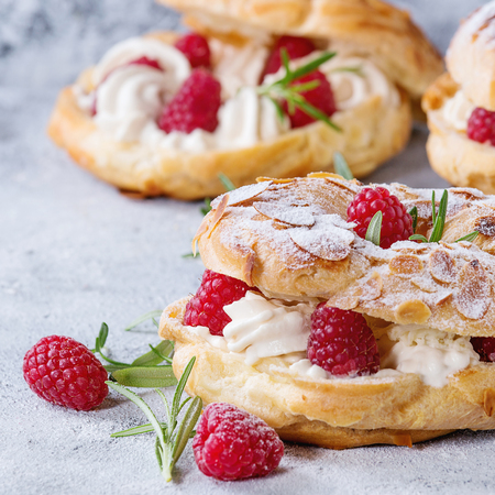Homemade choux pastry cake Paris Brest with raspberries, almond, sugar powder and rosemary, served over gray blue texture background.