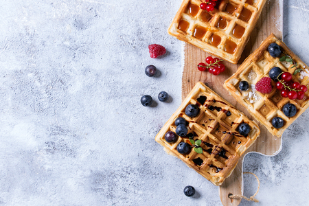 Homemade square belgian waffles with fresh ripe berries blueberry, raspberry, red currant served with caramel, balsamic sauce on wooden serving board over gray background. Top view with space