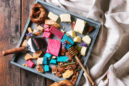 lavender coloured: Variety of colorful holland cheese traditional soft, old, pink basil, blue lavender served with pecan nuts, honey, lavender flowers, pretzels bread on tray over wooden planks background. Flat lay