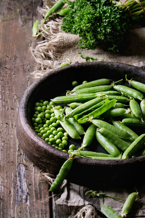 Young organic green pea pods and peas in terracotta tray and bundle of parsley over old dark wooden planks with sackcloth textile background. Harvest, healthy eating. Banco de Imagens
