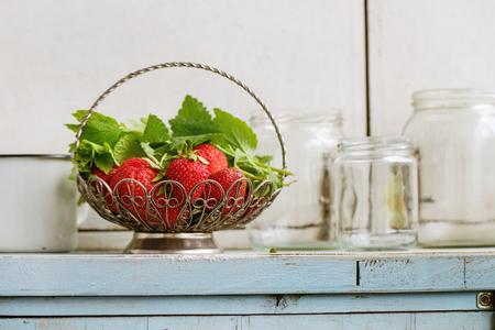 新鮮な熟した庭いちごは、青い白い木製キッチン テーブルの上ジャムの空のガラス瓶を花瓶ヴィンテージ状態でメリッサ ハーブ。素朴なスタイル、
