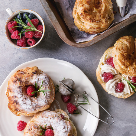 Filling and empty homemade choux pastry cake Paris Brest with raspberries, almond, sugar powder, rosemary on plate and oven tray with berries over gray texture background. Flat lay. Square image Archivio Fotografico
