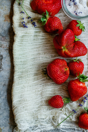 Fresh ripe organic strawberries prepared for making jam. Served with sugar, lavender on gauze over gray metal background.