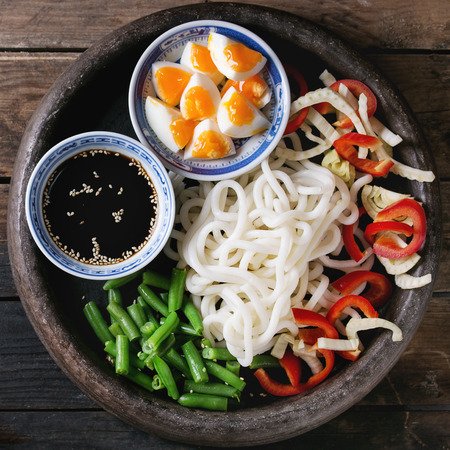 Ingredients for cooking stir fry udon noodles, green beans, sliced paprika, boiled eggs, soy sauce with sesame seeds in traditional bowls in terracotta tray over wooden background. Flat lay. Square image Reklamní fotografie