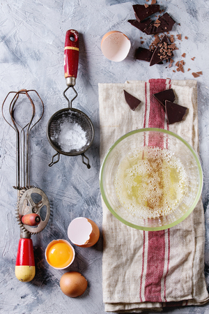 Ingredients and utensils for cooking meringue. Whipped egg whites, sugar powder, broken eggs, vintage sieve and hand mixer on linen towel over gray texture background. Top view. Baking dessert concept