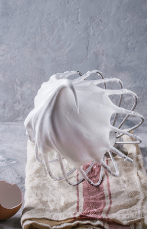 Process of cooking meringue. Whipped egg whites on mixer whisk with broken eggs on linen towel over gray texture background. Baking dessert concept. Close up