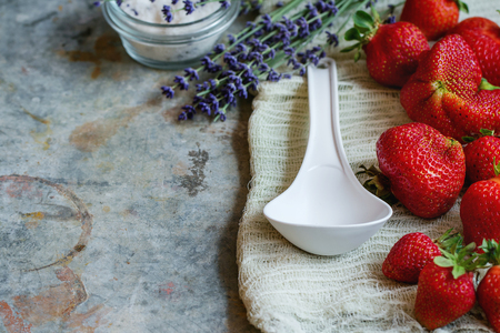 Fresh ripe strawberries prepared for making jam. Served with sugar, lavender and big white plastic spoon on gauze over gray metal background. Preserving concept. Rustic style, day light Stock Photo