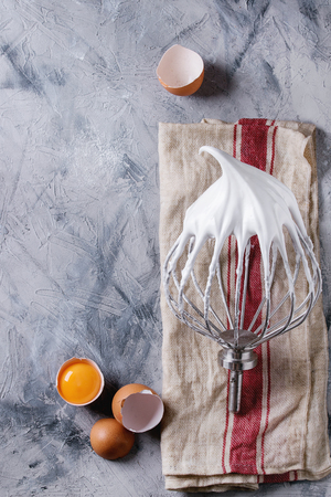 Process of cooking meringue. Whipped egg whites on mixer whisk with broken eggs on linen towel over gray texture background. Top view. Baking dessert concept Reklamní fotografie