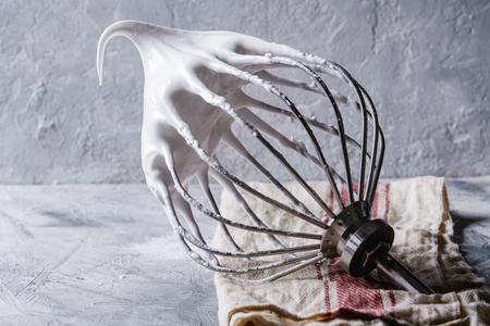 머랭을 요리하는 과정. 회색 질감 배경 위에 린 넨 수건에 믹서 털에 달걀 흰 채찍을 휘저어 진. 베이킹 디저트 개념입니다. 닫다