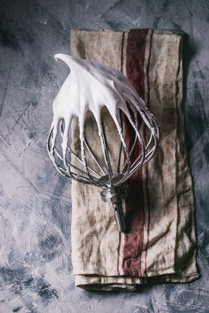 Process of cooking meringue. Whipped egg whites on mixer whisk on linen towel over gray texture background. Top view. Baking dessert concept Reklamní fotografie