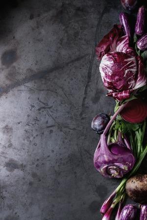 Assortiment ruw organisch van paarse groenten mini-aubergines, lente-ui, biet, radicchio salade, pruimen, kohlrabi, bloemzout op donkere metaalachtergrond. Bovenaanzicht met de ruimte
