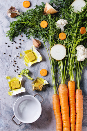 Raw vegetables and bouillon cubes for cooking soup. Young carrot with haulm, broccoli, cauliflower, onion, garlic, salt pepper empty pot over gray concrete background. Top view. Dinner cooking concept