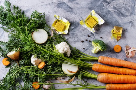 Raw vegetables and bouillon cubes for cooking soup. Young carrot with haulm, broccoli, cauliflower, onion, garlic, salt pepper over gray concrete background. Top view. Dinner cooking concept Фото со стока - 83387718