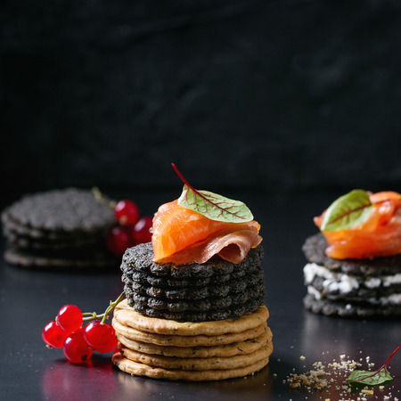 Stack of black wholegrain charcoal and traditional crackers with smoked salmon, cream cheese, green salad and red currant berries over black metal background. Appetizer snack. Square image Stok Fotoğraf - 83650864