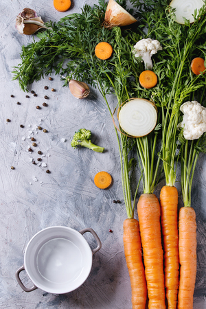 Raw vegetables for cooking soup. Ingredients young carrot with haulm, broccoli, cauliflower, onion, garlic, salt pepper, empty pot over gray concrete background. Top view. Dinner cooking concept