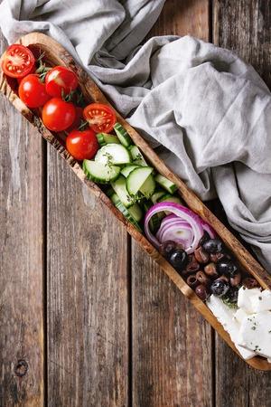 Ingrediënten voor traditionele Griekse salade. Kersentomaten, Gesneden Komkommers, Rode Ui, Zwarte Olijven, Feta Kaas In Olijfhoutkom Met Grijze Textiel Over Houten Plankachtergrond. Bovenaanzicht