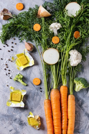 Raw vegetables and bouillon cubes for cooking soup. Young carrot with haulm, broccoli, cauliflower, onion, garlic, salt pepper over gray concrete background. Top view. Dinner cooking concept Фото со стока