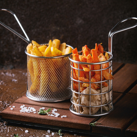 Variety of french fries traditional potatoes, sweet potato, carrot served in frying basket with salt, thyme on wooden board over brown texture background. Homemade fast food. Square image