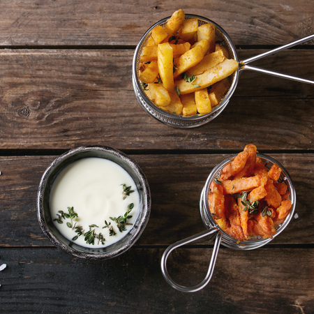 Variety of french fries traditional potatoes, sweet potato, carrot served in frying basket with white cheese sauce, salt, thyme over old wooden background. Top view with space. Square image