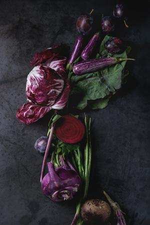 Sortiment rohe Bio von lila Gemüse Mini Auberginen, Frühlingszwiebeln, Rote Beete, Radicchio Salat, Pflaumen, Kohlrabi, Blüten Salz über dunklen Metall Hintergrund. Draufsicht mit Platz Standard-Bild - 83414610