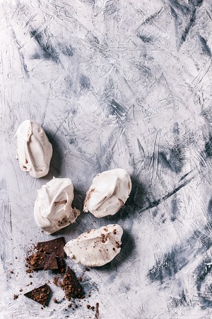 Baking homemade french dessert meringue with chocolate served with dark chopping chocolate and cocoa powder over gray concrete texture background. Top view with copy space