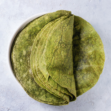 Stack of empty green spinach matcha tortillas in terracotta plate over gray texture background. Flat lay. Square image Stock Photo