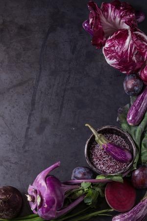 Assortiment rauwe biologische van paarse groenten mini-aubergines, lente-ui, rode biet, radicchio salade, pruimen, koolrabi, bloemzout over donkere metalen achtergrond. Bovenaanzicht met ruimte. Voedselkader Stockfoto