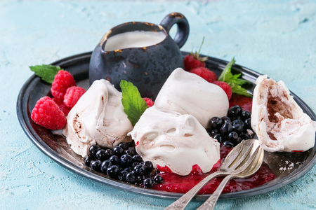 Traditional summer dessert Eton Mess. Meringue, jug of cream, berry jam, fresh blueberries, raspberries on vintage tray, decorated with mint leaves over light blue concrete background.