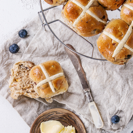 Hot cross buns on baking rack served with butter, fresh blueberries, knife and jug of cream on textile napkin over white texture concrete background. Top view, space. Easter baking. Square image