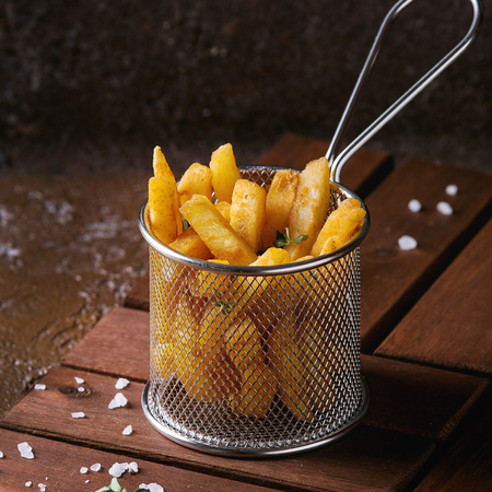 Traditional french fries potatoes served in frying basket with salt, thyme on wooden board over brown texture background. Homemade fast food. Square image