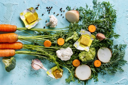 Raw vegetables and bouillon cubes for cooking soup. Young carrot with haulm, broccoli, cauliflower, onion, garlic, salt pepper over turquoise concrete background. Top view. Dinner cooking concept Фото со стока - 83650548