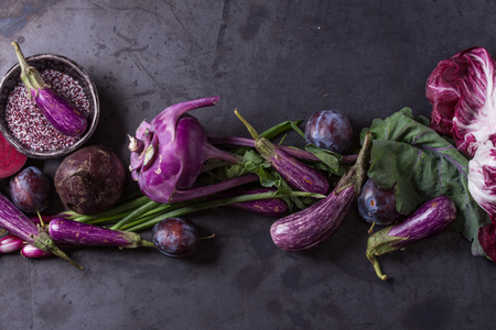 Assortment raw organic of purple vegetables mini eggplants, spring onion, beetroot, radicchio salad, plums, kohlrabi, flower salt over dark metal background. Top view with space Stock Photo