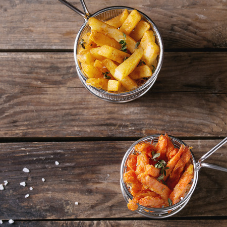 Variety of french fries traditional potatoes, sweet potato, carrot served in frying basket with salt, thyme over old wooden background. Top view with space. Homemade fast food. Square image