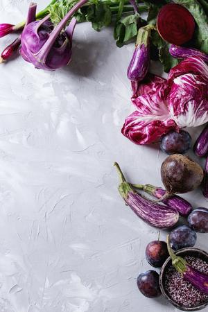 Assortiment rauwe biologische van paarse groenten mini-aubergines, lente-ui, rode biet, radicchio salade, pruimen, koolrabi, bloemzout over grijze concrete achtergrond. Bovenaanzicht met ruimte. Voedselkader Stockfoto