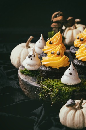 Halloween decorated sweet dessert table black cupcake with orange cream, white meringue ghosts with chocolate eyes, decor skulls and pumpkin on clay plate  over black background. Toned image