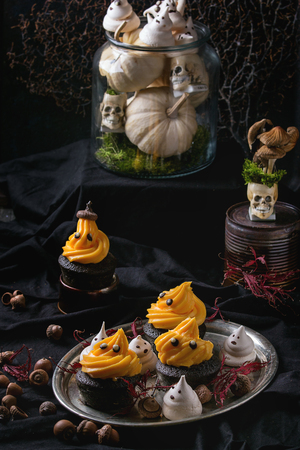 Halloween decorated sweet dessert table black cupcake with orange cream, white meringue ghosts with chocolate eyes on metal tray, leaves acorn decor skulls and pumpkin over black tablecloth.