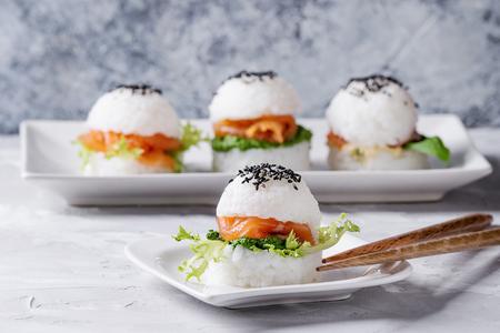スモーク サーモン、グリーン サラダ、ソース、黒こまとミニご飯寿司ハンバーガー灰色コンクリート背景の上には木の箸で白い正方形平板の提供を 写真素材
