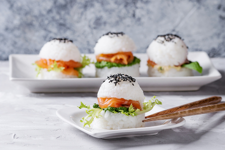 Mini rice sushi burgers with smoked salmon, green salad and sauces, black sesame served on white square plate with wooden chopsticks over gray concrete background. Modern healthy food
