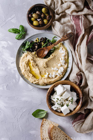 Homemade traditional spread hummus with chopping olives, oil and herbs on blue plate, served with bread, olives, feta cheese, spoon, textile on gray texture background. Mediterranean snack. Flat lay Stock Photo