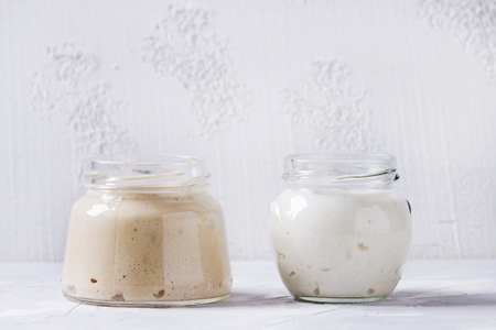 Rye and wheat starter sourdough in glass jars for baking homemade bread over gray concrete background. Banco de Imagens