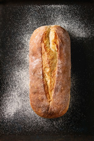 Whole homemade white wheat bread with wheat flour on old black oven tray as background. Top view Stock Photo