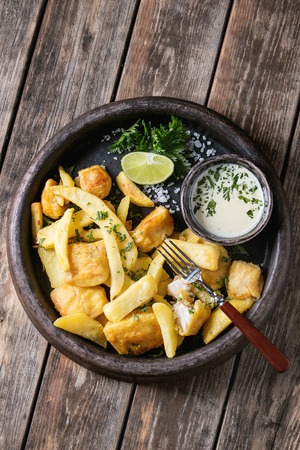 Traditional british fast food fish and chips. Served with white cheese sauce, lime, parsley, fork in terracotta tray over old wooden plank background. Top view with space Stock Photo