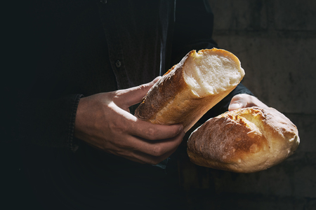 Loaf of fresh baked wheat bread in mans hands in sunshine. Rustic day light in dark room. Toned image