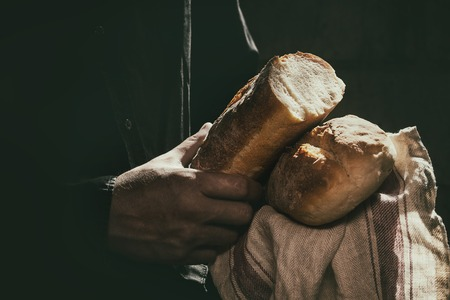 man's: Loaf of fresh baked wheat bread in mans hands in sunshine. Rustic day light in dark room. Toned image