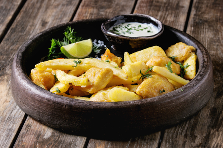Traditional british fast food fish and chips. Served with white cheese sauce, lime, parsley in terracotta tray over old wooden plank background. Close up Stock Photo