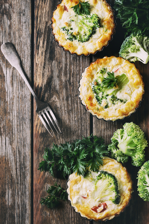 Baked homemade quiche pie in mini metal forms served with fresh greens and fork on old plank wooden background. Flat lay with space Stock Photo