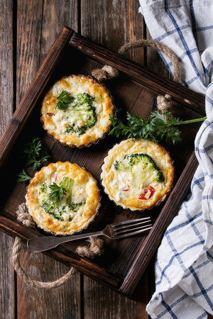 Baked homemade quiche pie in mini metal forms served with fresh greens, kitchen towel and fork in dark wood tray on old plank wooden background. Flat lay with space Reklamní fotografie - 84146648