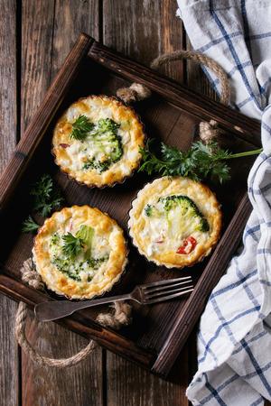 Gebakken zelfgemaakte quiche pie in mini-metalen vormen geserveerd met verse greens, keukendoek en vork in donker hout lade op oude plank houten achtergrond. Plat leggen met ruimte